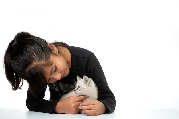 Niña sonriente con gatito blanco aislado