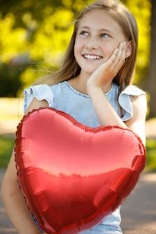 Niña sonriente con un globo en forma de corazón en la naturaleza