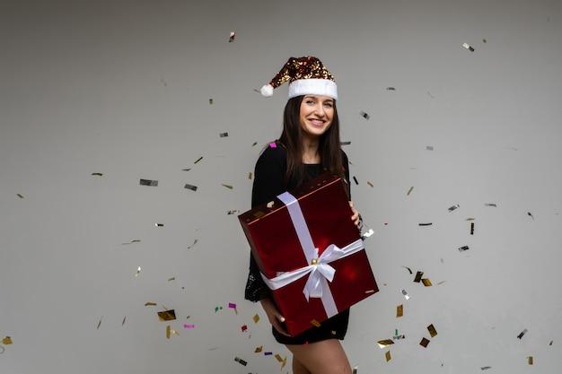 Niña sonriente con gran regalo festivo apuntando con la mano en el espacio vacío con confeti de vacaciones sobre fondo gris