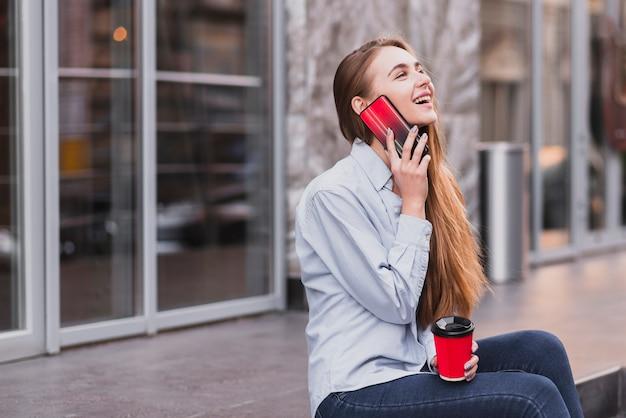 Niña sonriente hablando por teléfono