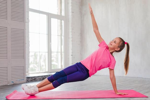 Niña sonriente haciendo ejercicios de estiramiento en el gimnasio
