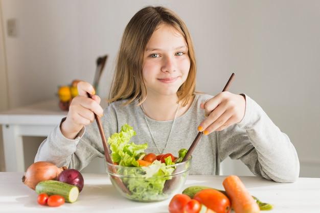 Niña sonriente haciendo ensalada de vegetales saludables