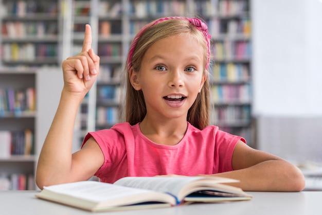 Niña sonriente haciendo sus deberes en la biblioteca