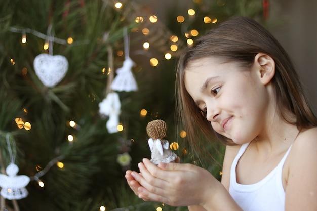 Niña sonriente hermosa que adorna el árbol de navidad y que sostiene la muñeca del ángel en su mano