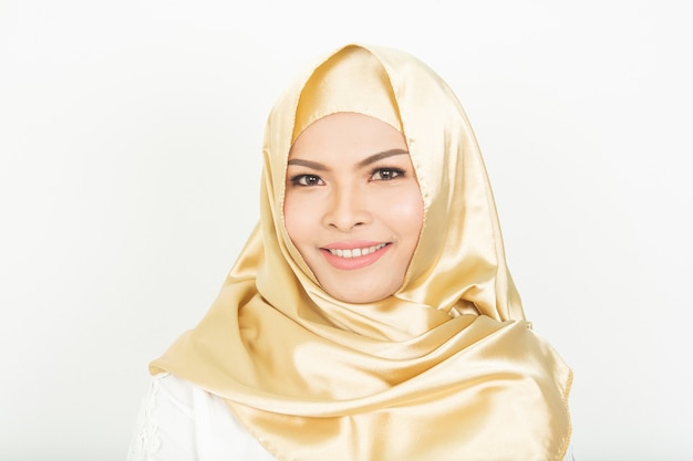 Niña sonriente en hijab cubriendo hermoso con felicidad y pared de color