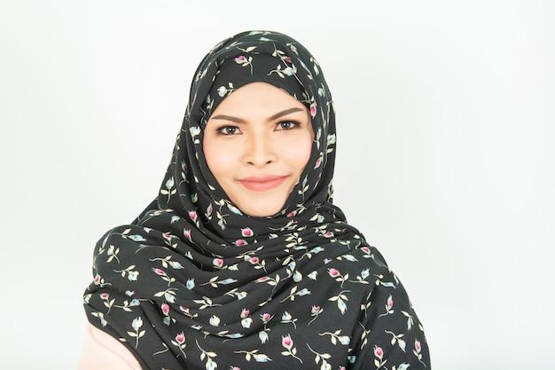 Niña sonriente en hijab que cubre hermosa con felicidad y pared de color