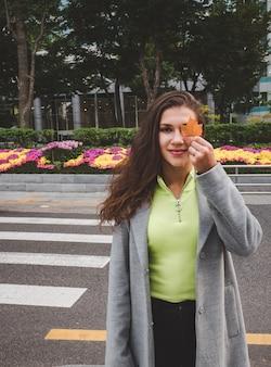 Niña sonriente con hoja de otoño en seúl