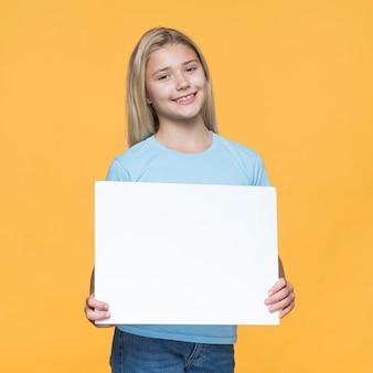 Niña sonriente con hoja de papel en blanco