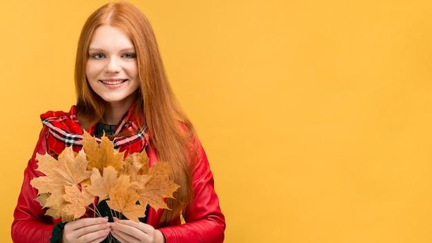 Niña sonriente con hojas y espacio de copia