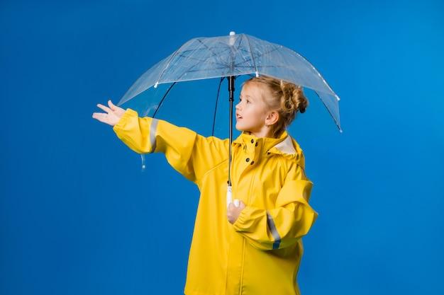 Niña sonriente en un impermeable amarillo y botas de goma con un paraguas