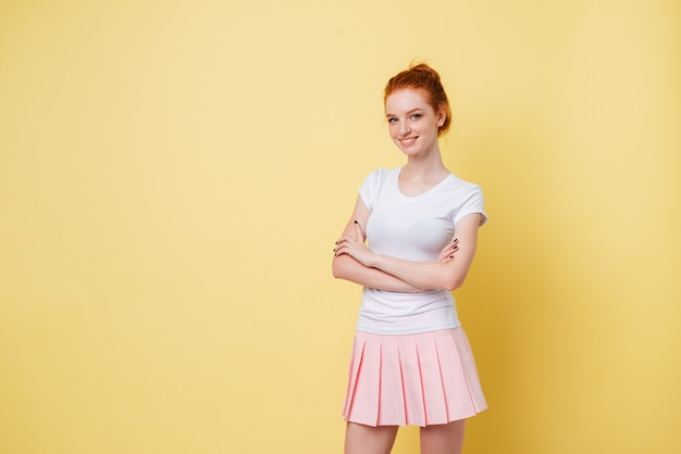 Niña sonriente de jengibre en camiseta y falda posando con los brazos cruzados y mirando