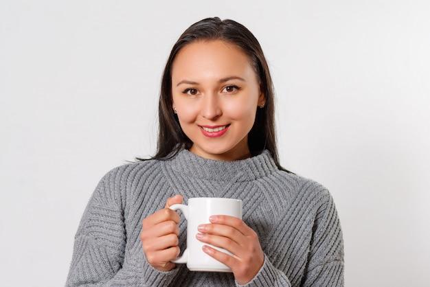 Niña sonriente joven morena en un suéter caliente con una taza de café caliente