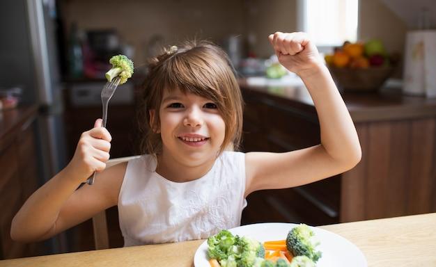 Niña sonriente jugando con comida