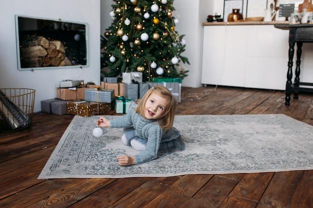 Niña sonriente jugando con decoración navideña