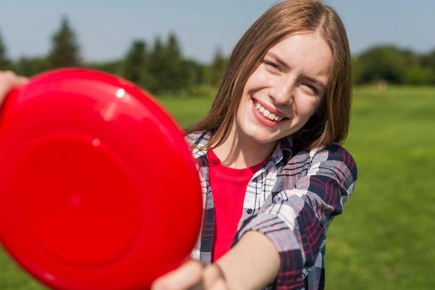 Niña sonriente jugando con frisbee rojo