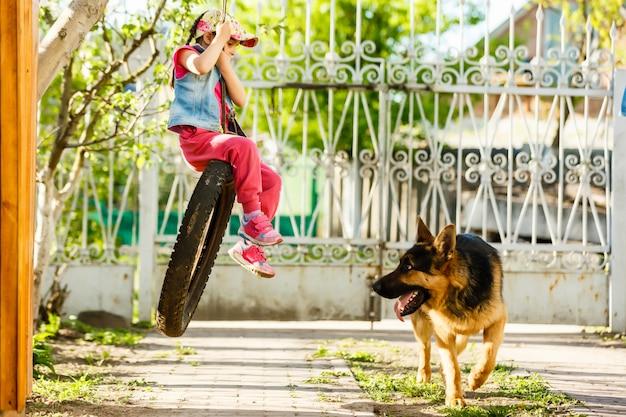 Niña sonriente jugando con perro fuera de casa de campo mirando a cámara, niño acariciando acariciando al pastor alemán en el porche al aire libre