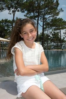 Niña sonriente jugando sentado piscina al aire libre