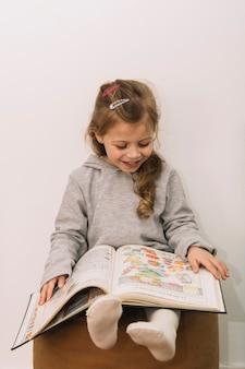 Niña sonriente leyendo en el puf