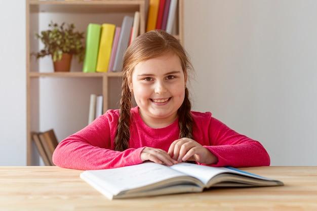Niña sonriente leyendo