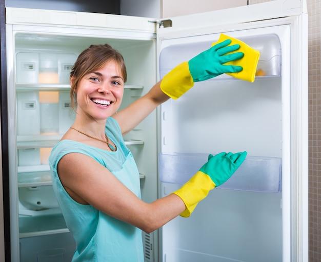 Niña sonriente limpiando el refrigerador