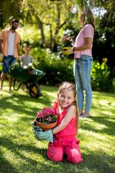 Niña sonriente con maceta en el patio