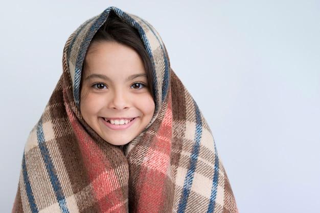 Niña sonriente con manta de invierno