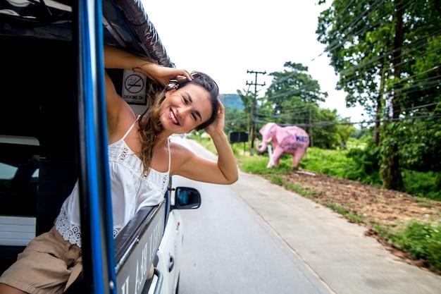 Niña sonriente mira por la ventana de un taxi, concepto de viaje en tuk-tuk