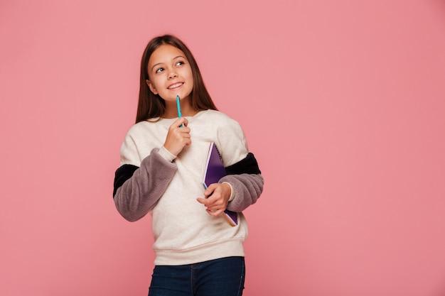 Niña sonriente mirando hacia arriba y pensando mientras sostiene un lápiz y libros