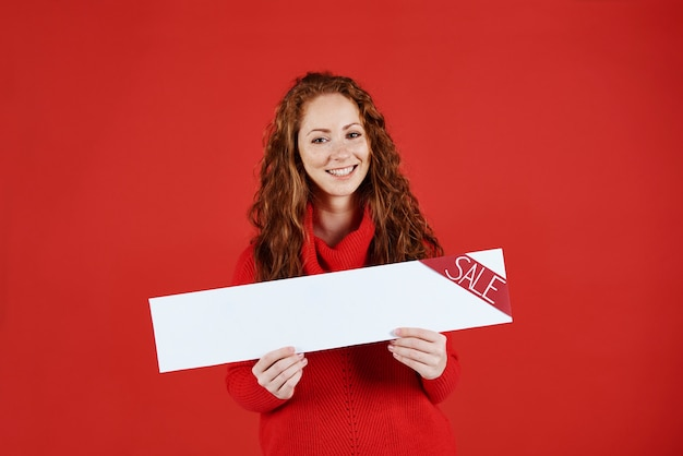 Niña sonriente mostrando banner vacío de venta