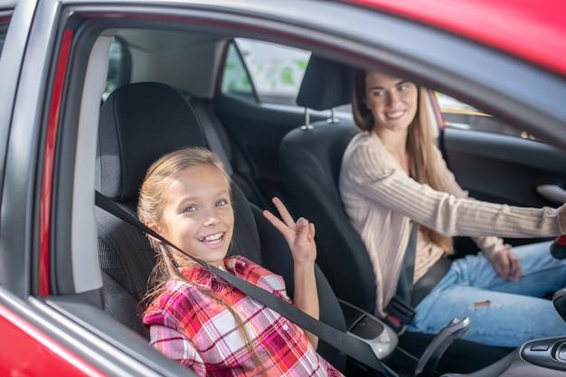 Niña sonriente mostrando el signo de la paz en el asiento del pasajero, yendo en coche con su mamá