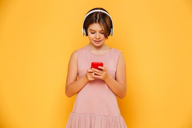 Niña sonriente ocupada con smartphone y auriculares aislados