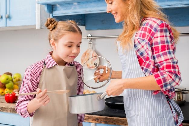 Niña sonriente oliendo la comida preparada por su madre.