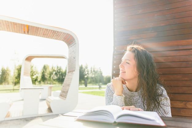 Niña sonriente en el parque con el libro. libro de lectura de la mujer en el banco
