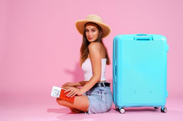 Niña sonriente con un pasaporte y dinero de boletos va a viajar sentado cerca de la maleta en pantalones cortos con ...