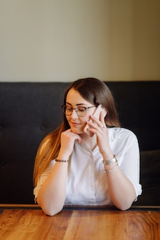 Niña sonriente pasar tiempo en un café de la calle con gadget digital