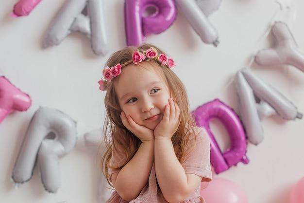 Niña sonriente con el pelo largo sobre un fondo blanco con globos