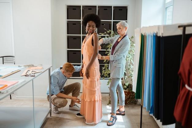 Niña sonriente de pie en un taller con un vestido de verano