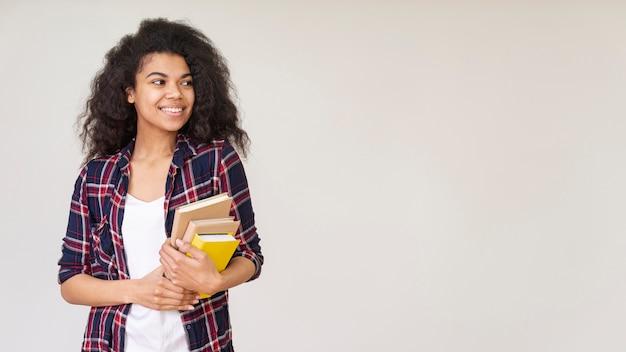 Niña sonriente con pila de libros