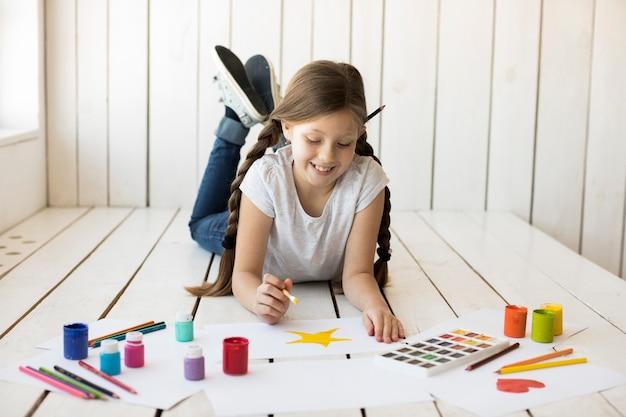 Niña sonriente pintando la estrella amarilla sobre papel blanco