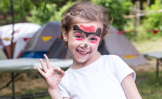 Niña sonriente con pintura de arte de cara como tigre, niño pequeño haciendo pintura de cara, fiesta de halloween, niño con pintura de cara divertida