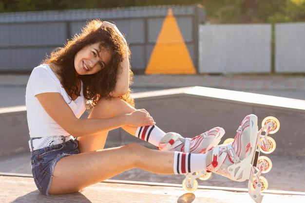 Niña sonriente posando en sus patines al aire libre