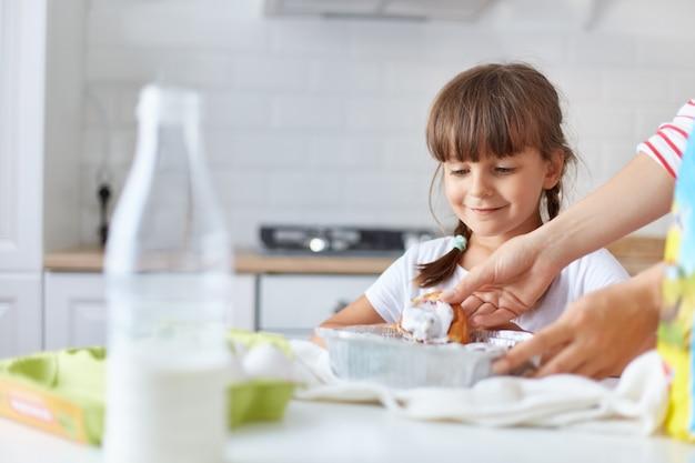 Niña sonriente positiva con dos coletas de pie junto a la mesa, esperando a su madre dándole un horneado sabroso caliente, niña con camiseta blanca posando en la cocina.