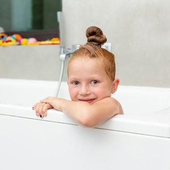 Niña sonriente de primer plano en la bañera