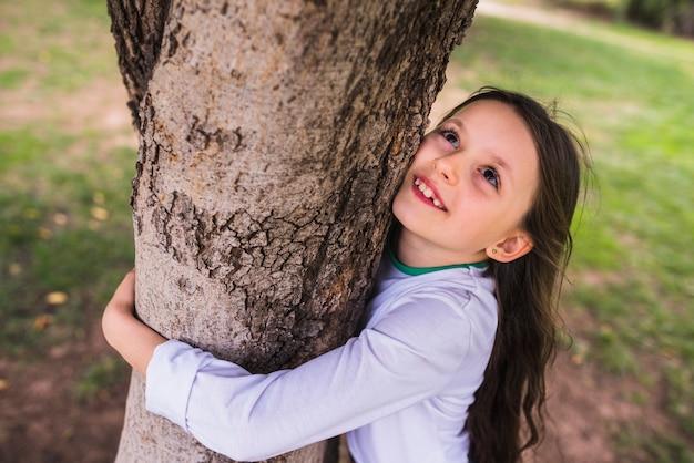 Niña sonriente que abraza el árbol en jardín