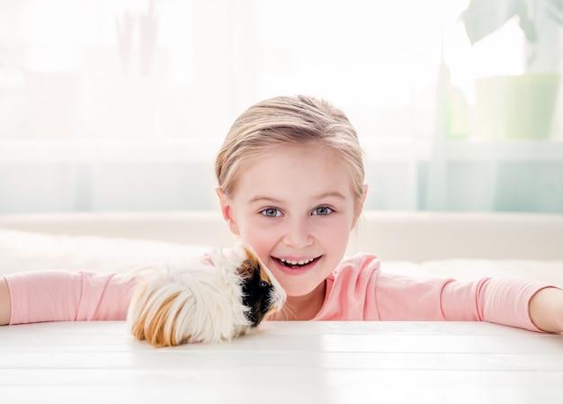 Niña sonriente que abraza el conejillo de indias