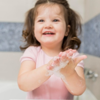 Niña sonriente que se lava las manos