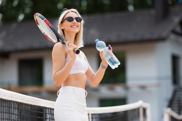 Niña sonriente con raqueta de tenis y agua