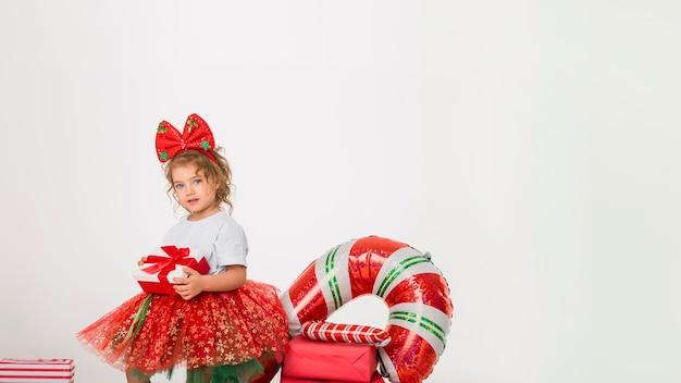 Niña sonriente rodeada de elementos navideños con espacio de copia