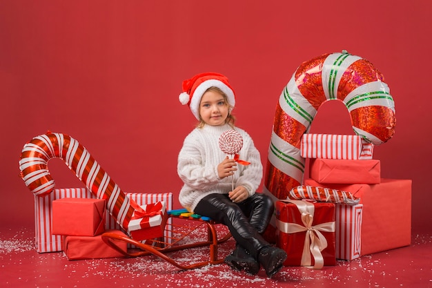 Niña sonriente rodeada de elementos y regalos de navidad