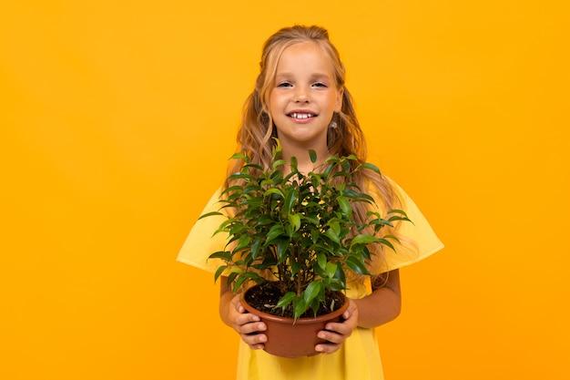 Niña sonriente rubia con flores en una pared de naranja